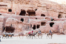 homes carved into red rock cliffs and camels