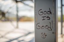 """""""God is good"""" handwritten on a metal pole."""