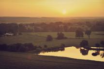 farmland and a pond at sunrise