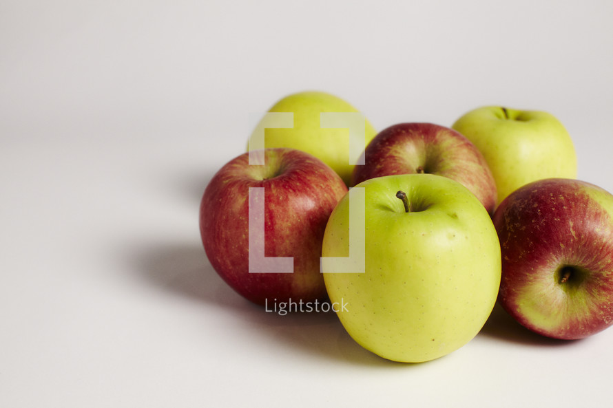 A cluster of green and red apples on seamless white
