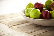 A bowl of red and green apples on a kitchen table