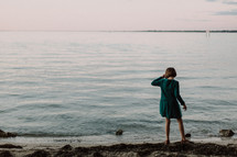 a girl child in a dress standing on a shore