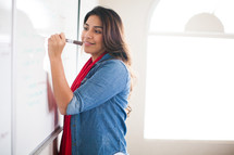 a woman writing on a dry erase board