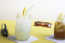 lemonade and iced tea on a table with sunglasses