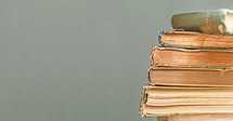 Stack of old books on a teal background