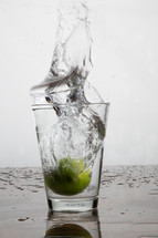 Water splashing out of a glass as a lime is dropped into the glass.