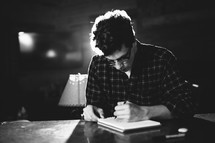 man writing on a notepad