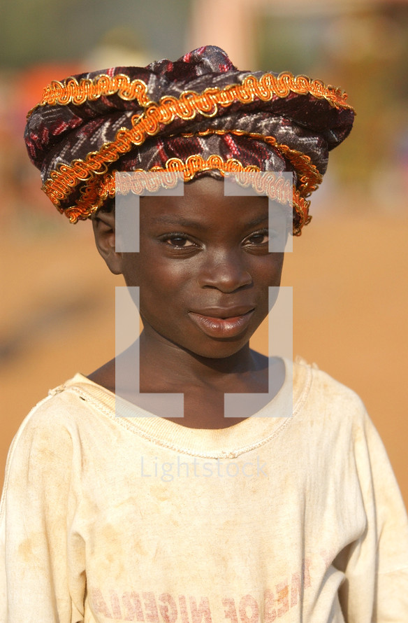 African child standing wearing a native hat