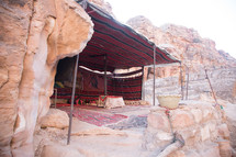 tent against a red rock cliff in Petra
