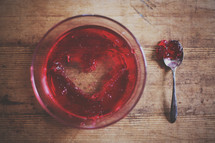 A bowl of red jello with a heart shape spooned out.