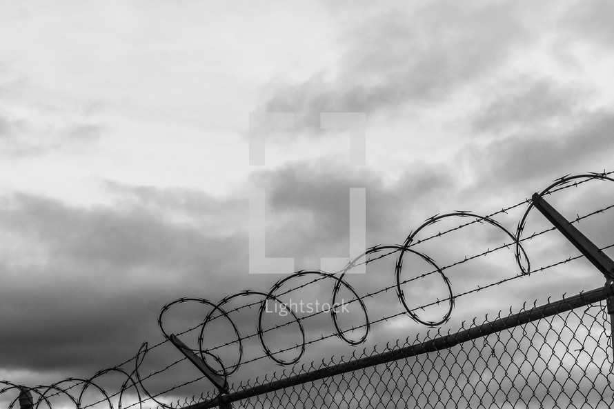 barbed wire on the top of a chain link fence under a gray sky