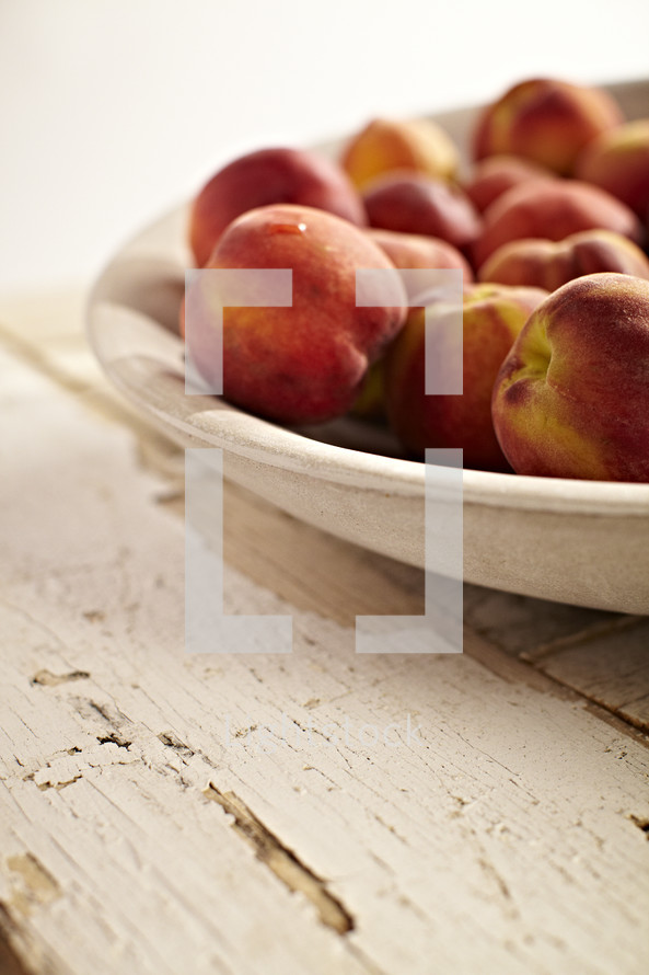 A bowl of peaches sit on an old wooden table.