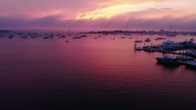 Boats in a bay under a deep purple sunset.