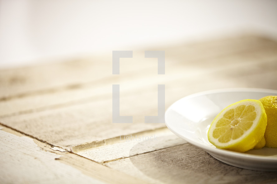 Two halves of a lemon sitting on a plate on a wooden table
