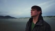 a sad man walking on a beach