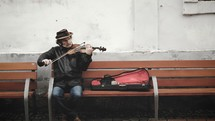 a man sitting on a bench playing a violin