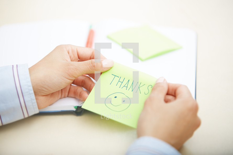 woman holding a sticky note with the word thanks