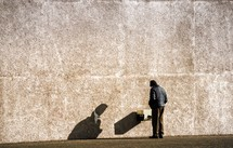 a man in a coat looking at a box against a wall