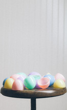 Colorful plastic Easter eggs on a wooden stool.