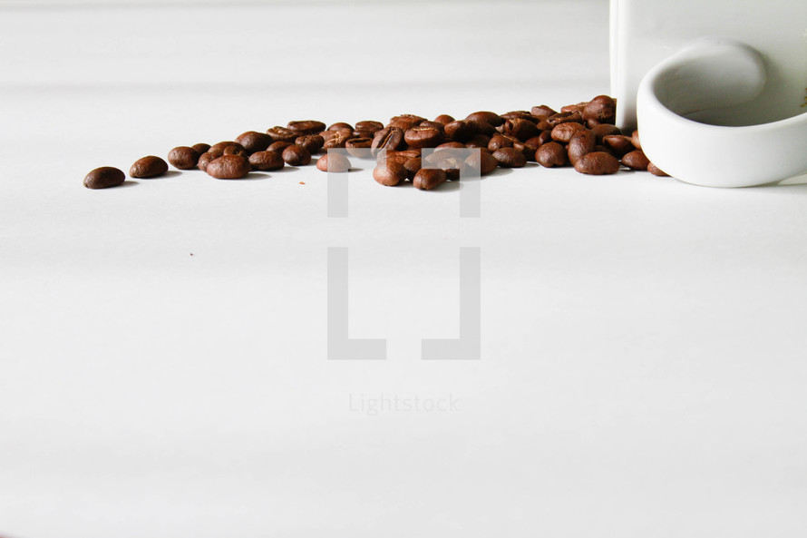 coffee beans spilled out of a coffee mug