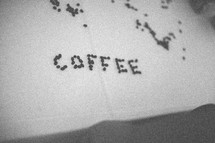 """Coffee"" spelled out in coffee beans on a table covered with white linen."