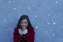a teen girl catching snowflakes