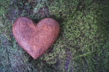heart shaped stone on moss