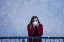 a teen girl drinking a mug in the snow