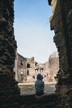 a child sitting in the ruins of a castle