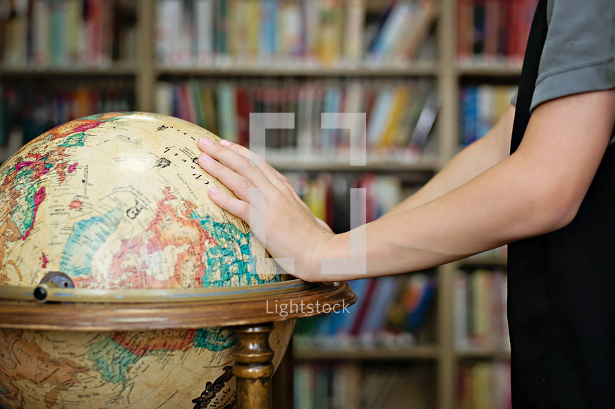 Hands on a world globe in a library.