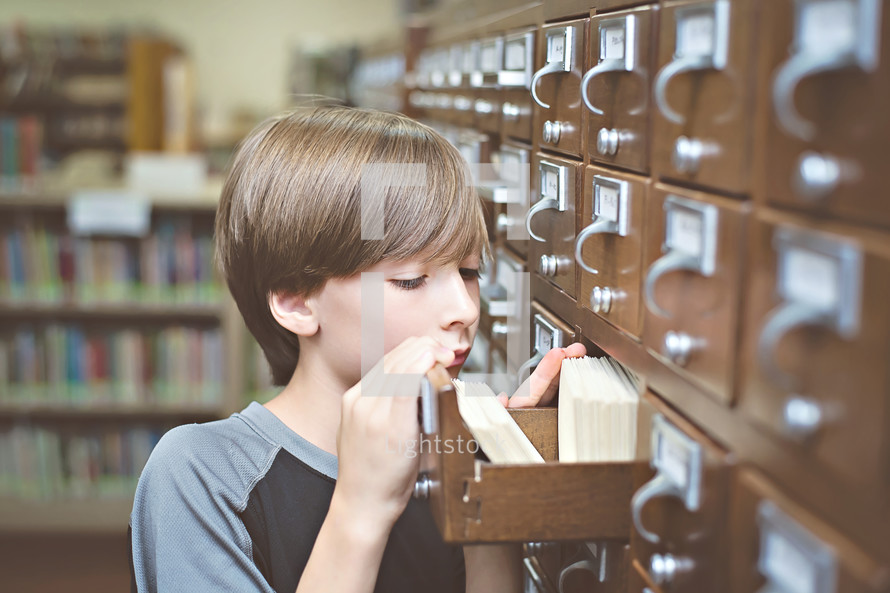 Boy looking in a drawer of a library card catalog cabinet.