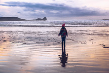 a girl in a winter coat walking on wet sand along a shore