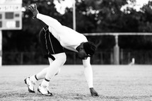 a man stretching on a football field