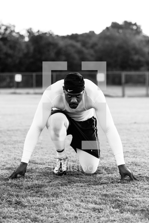 a man in a runner's stance on a wet field