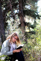 A woman sits and reads her Bible in a forest.