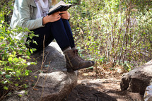 A woman sits outdoors on a rock and reads her Bible.