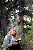 A young woman reads her Bible and thinks in a forest.