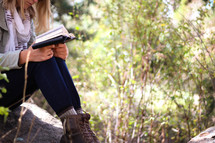 A young woman sits in the woods and reads her Bible.
