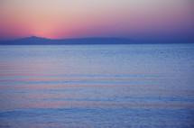 ocean at sunset under a pink sky