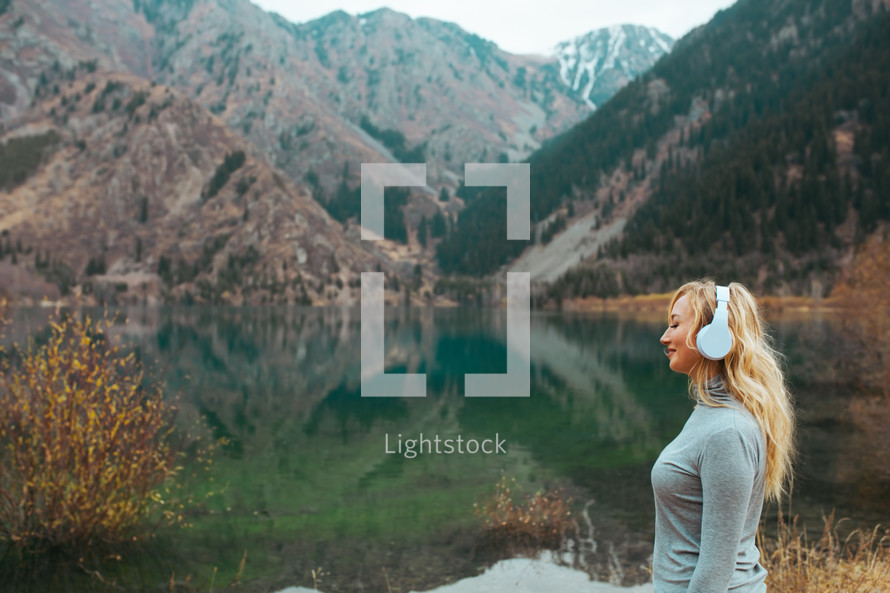 woman listening to headphone by a lake shore