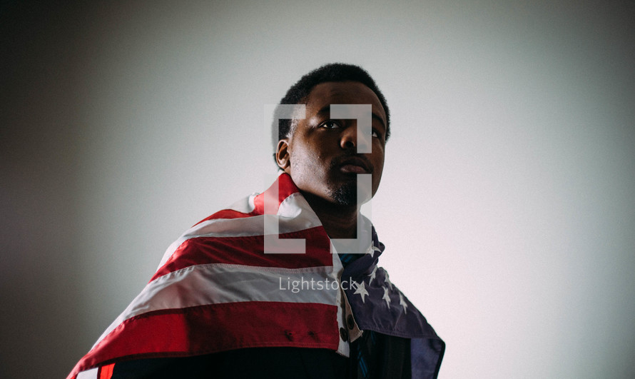 An African American man wrapped in an American flag