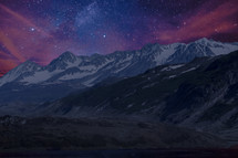 stars in the night sky over snow capped mountains