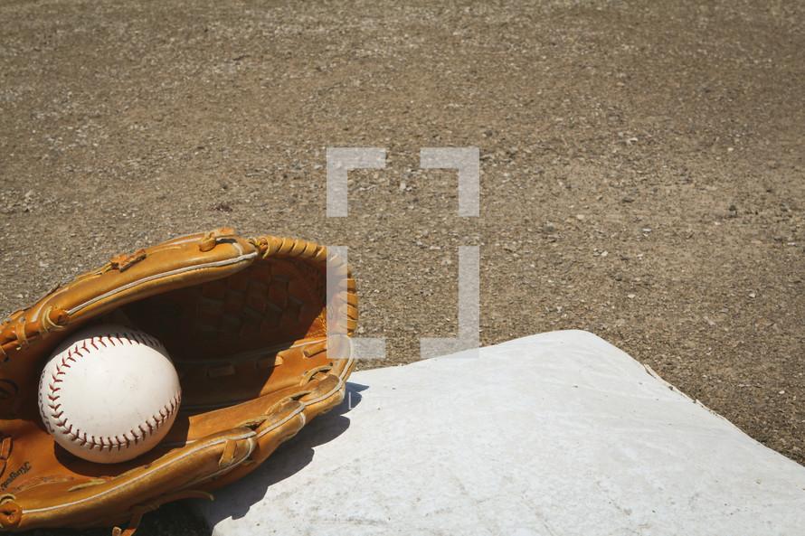 a softball and glove on a base