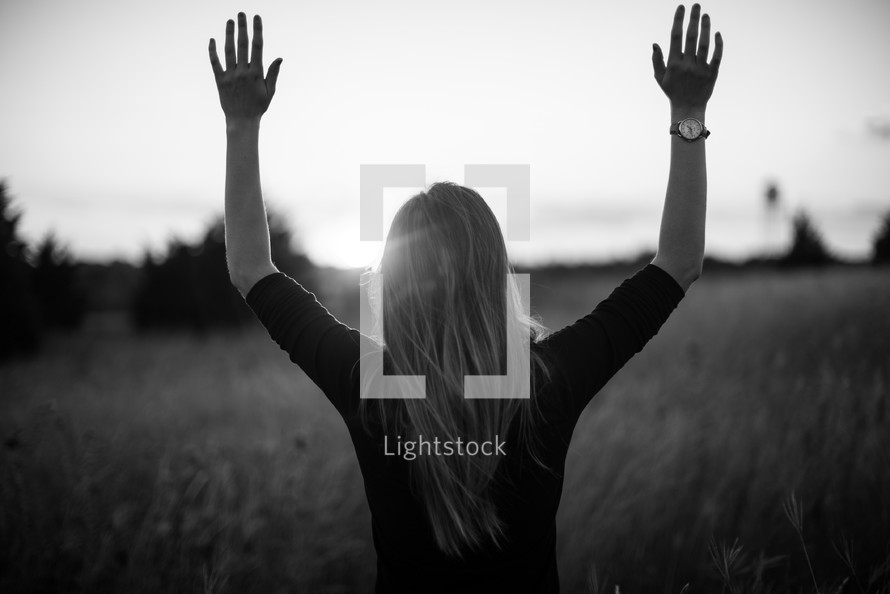 a woman standing in a field with hands raised