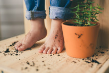 kid's feet and a potted plant
