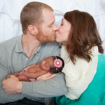 Kissing couple holding a newborn infant.