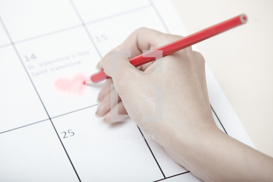 drawing a heart on a calendar for Valentines day