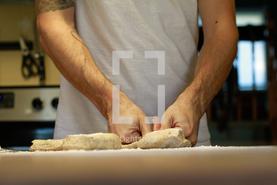 a man shaping dough in a kitchen