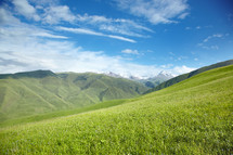 snow capped mountains and green rolling hills