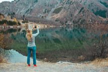 woman taking a picture of a pond
